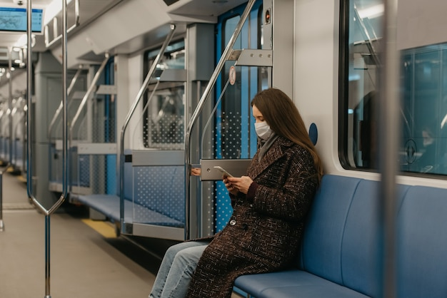 Kobieta w medycznej masce na twarz, aby uniknąć rozprzestrzeniania się koronawirusa, siedzi i korzysta ze smartfona w nowoczesnym wagonie metra. dziewczyna w masce chirurgicznej przewija wiadomości na swoim telefonie w pociągu.