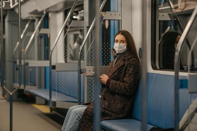 Kobieta w medycznej masce na twarz, aby uniknąć rozprzestrzeniania się koronawirusa, siedzi i patrzy z boku na nowoczesny wagon metra. dziewczyna w masce chirurgicznej przeciwko covid-19 jedzie pociągiem metra.