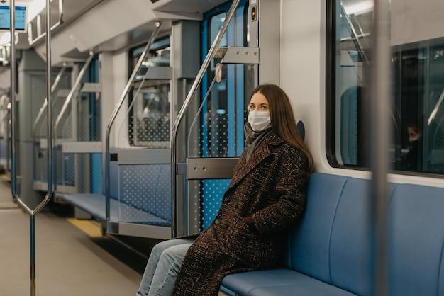 Kobieta w medycznej masce na twarz, aby uniknąć rozprzestrzeniania się koronawirusa, siedzi samotnie w nowoczesnym wagonie metra. dziewczyna w masce chirurgicznej trzyma dystans społeczny w pociągu metra.