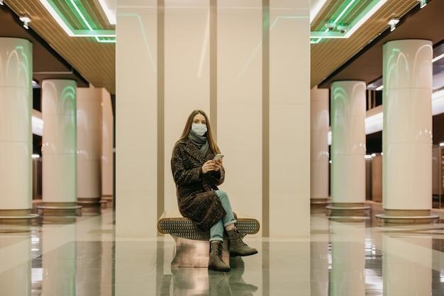 Kobieta w medycznej masce na twarz, aby uniknąć rozprzestrzeniania się koronawirusa, siedzi ze smartfonem i czeka na pociąg metra. dziewczyna w masce chirurgicznej trzyma dystans w metrze.