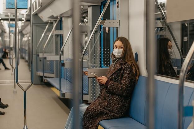 Kobieta w medycznej masce na twarz, aby uniknąć rozprzestrzeniania się koronawirusa, siedzi ze smartfonem w nowoczesnym wagonie metra. dziewczyna w masce chirurgicznej przeciwko covid-19 jedzie pociągiem metra.