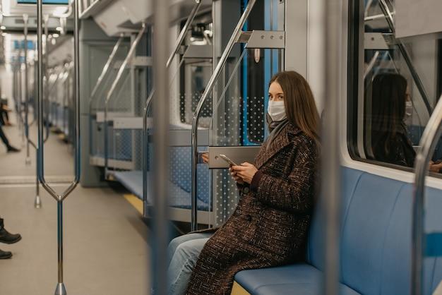 Kobieta w medycznej masce na twarz, aby uniknąć rozprzestrzeniania się koronawirusa, siedzi ze smartfonem w nowoczesnym wagonie metra. dziewczyna w masce chirurgicznej przeciwko covid-19 jedzie pociągiem.