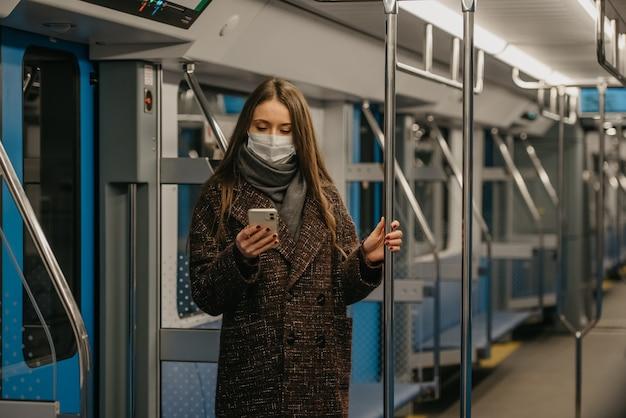 Kobieta w medycznej masce na twarz, aby uniknąć rozprzestrzeniania się koronawirusa, stoi i korzysta ze smartfona w pustym wagonie metra. dziewczyna w masce chirurgicznej przewija wiadomości na swoim telefonie komórkowym w pociągu.