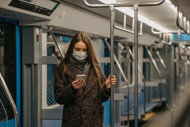 Kobieta w medycznej masce na twarz, aby uniknąć rozprzestrzeniania się koronawirusa, stoi i korzysta ze smartfona w pustym wagonie metra. dziewczyna w masce chirurgicznej przewija wiadomości na swoim telefonie w pociągu.