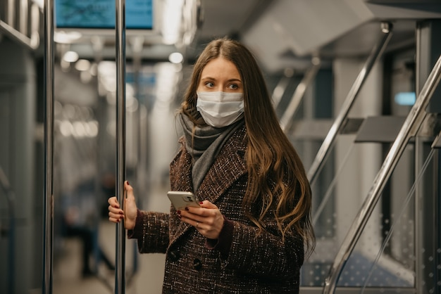 Kobieta w medycznej masce na twarz, aby uniknąć rozprzestrzeniania się koronawirusa, stoi i patrzy w bok w nowoczesnym wagonie metra. dziewczyna w masce chirurgicznej przeciwko covid-19 jedzie pociągiem metra