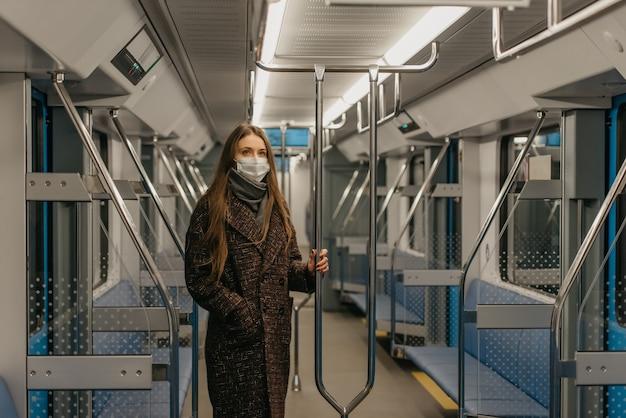 Kobieta w medycznej masce na twarz, aby uniknąć rozprzestrzeniania się koronawirusa, stoi i trzyma poręcz w nowoczesnym wagonie metra. dziewczyna w masce chirurgicznej trzyma dystans społeczny w pociągu metra.