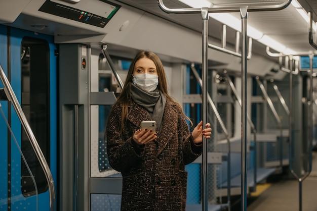 Kobieta w medycznej masce na twarz, aby uniknąć rozprzestrzeniania się koronawirusa, stoi i trzyma smartfon w nowoczesnym wagonie metra. dziewczyna w masce chirurgicznej przeciwko covid-19 jedzie pociągiem metra.