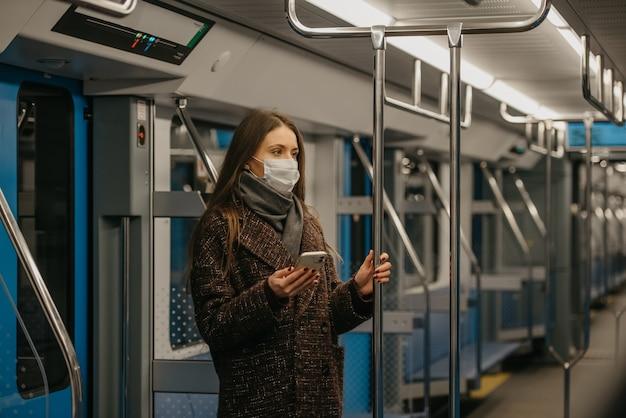 Kobieta w medycznej masce na twarz, aby uniknąć rozprzestrzeniania się koronawirusa, stoi i trzyma telefon w nowoczesnym wagonie metra. dziewczyna w masce chirurgicznej przeciwko covid-19 jedzie pociągiem metra.