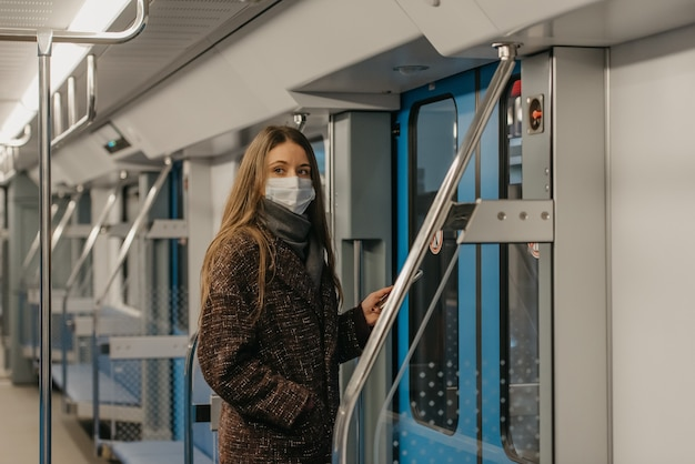 Kobieta w medycznej masce na twarz, aby uniknąć rozprzestrzeniania się koronawirusa, stoi przy drzwiach i patrzy w bok w nowoczesnym wagonie metra. dziewczyna w masce chirurgicznej jedzie pociągiem metra.