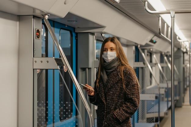 Kobieta w medycznej masce na twarz, aby uniknąć rozprzestrzeniania się koronawirusa, stoi przy drzwiach i patrzy w bok w pustym wagonie metra. dziewczyna w masce chirurgicznej jedzie pociągiem metra.