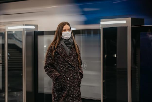 Kobieta w medycznej masce na twarz, aby uniknąć rozprzestrzeniania się koronawirusa, stoi w pobliżu odjeżdżającego pociągu na peronie metra. dziewczyna w masce chirurgicznej utrzymuje dystans społeczny na stacji metra.