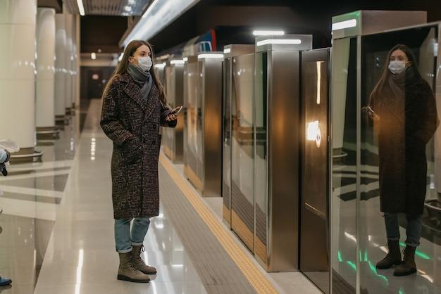 Kobieta w medycznej masce na twarz, aby uniknąć rozprzestrzeniania się koronawirusa, ukrywa smartfon w oczekiwaniu na pociąg na peronie metra. dziewczyna w masce chirurgicznej zachowuje dystans społeczny.