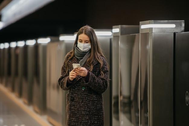 Kobieta w medycznej masce na twarz, aby uniknąć rozprzestrzeniania się koronawirusa, używa smartfona na peronie metra. dziewczyna w masce chirurgicznej trzyma dystans w metrze.