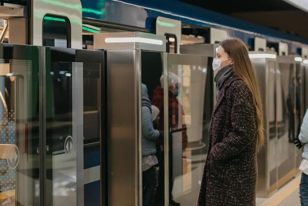 Kobieta w medycznej masce na twarz, aby uniknąć rozprzestrzeniania się koronawirusa, wchodzi do nowoczesnego metra. dziewczyna w masce chirurgicznej utrzymuje dystans społeczny na stacji metra.