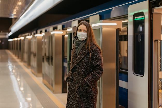 Kobieta w medycznej masce na twarz, aby uniknąć rozprzestrzeniania się koronawirusa, wysiada z nowoczesnego metra. dziewczyna w masce chirurgicznej utrzymuje dystans społeczny na stacji metra.