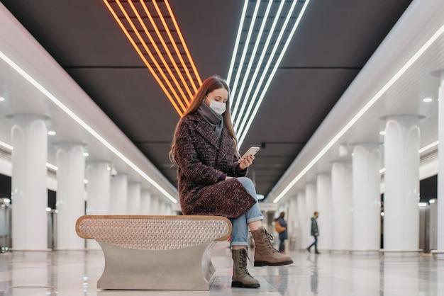 Kobieta w medycznej masce na twarz siedzi na środku dużej stacji metra ze smartfonem i czyta wiadomości. dziewczyna z długimi włosami w masce chirurgicznej trzyma dystans społeczny w metrze