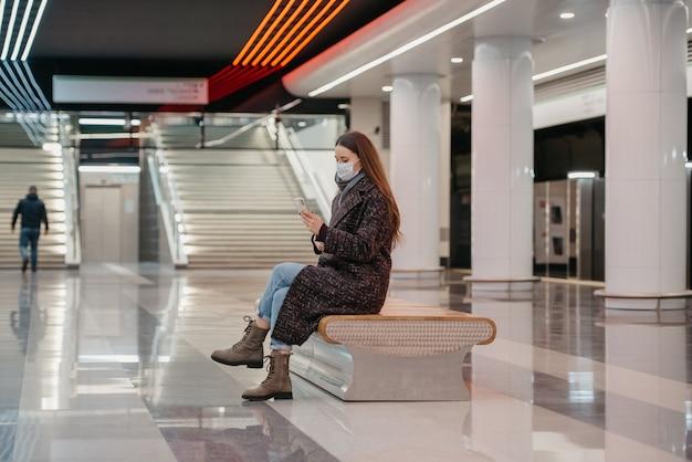 Kobieta w medycznej masce na twarz siedzi na środku peronu metra i używa smartfona. dziewczyna z długimi włosami w masce chirurgicznej utrzymuje dystans społeczny w metrze.
