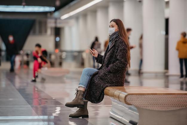 Kobieta w medycznej masce na twarz siedzi na środku peronu ze smartfonem i czeka na pociąg. dziewczyna w masce chirurgicznej trzyma dystans społeczny w metrze.