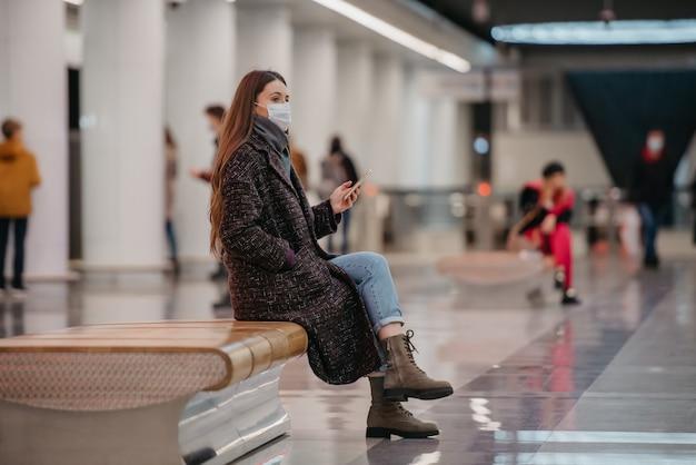 Kobieta w medycznej masce na twarz siedzi na środku peronu ze smartfonem i czeka na pociąg. dziewczyna w masce chirurgicznej trzyma dystans w metrze.