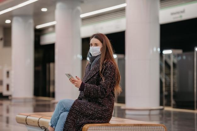 Kobieta w medycznej masce na twarz siedzi na środku peronu ze smartfonem i czeka na pociąg. dziewczyna z długimi włosami w masce chirurgicznej trzyma dystans społeczny w metrze
