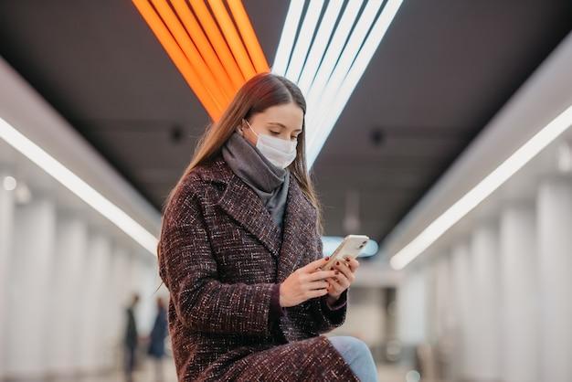 Kobieta w medycznej masce na twarz siedzi na środku peronu ze smartfonem i czyta wiadomości. dziewczyna z długimi włosami w masce chirurgicznej utrzymuje dystans społeczny w metrze.