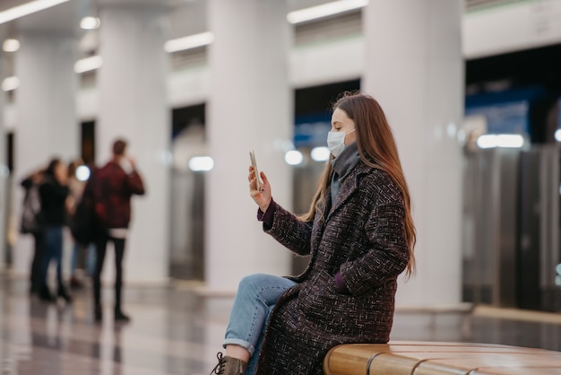 Kobieta w medycznej masce na twarz siedzi na środku platformy metra ze smartfonem i robi selfie. dziewczyna z długimi włosami w masce chirurgicznej trzyma dystans społeczny w metrze.