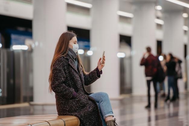 Kobieta w medycznej masce na twarz siedzi na środku platformy metra ze smartfonem i robi selfie. dziewczyna z długimi włosami w masce chirurgicznej utrzymuje dystans społeczny w metrze.