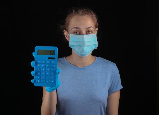 Kobieta w medycznej masce ochronnej, rękawiczki trzymają kalkulator na czarnej ścianie. covid-19, globalny kryzys