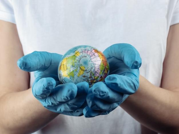 Kobieta w medycznych rękawice ochronne gospodarstwa glob na czarnej ścianie. pandemiczny kowid-19