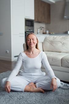 Kobieta w medytacji pozuje w domu koncepcja czasu i dobrego samopoczucia