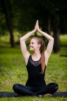 Kobieta w medytacji stanowią joga na zielonej trawie