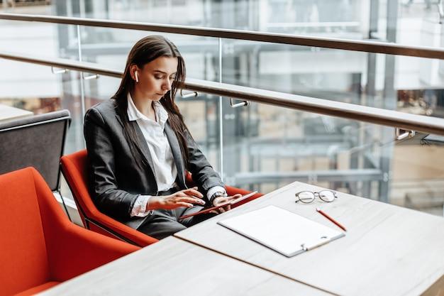 Kobieta w miejscu pracy czyta informacje na tablecie kobieta pracuje z dokumentami i szuka informacji w internecie