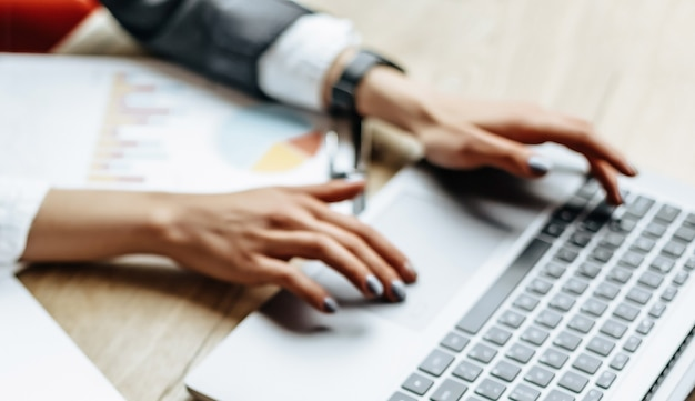 Kobieta w miejscu pracy w biurze w pobliżu notatnika. pomysł na biznes. kobieta pracuje na laptopie. godziny pracy.