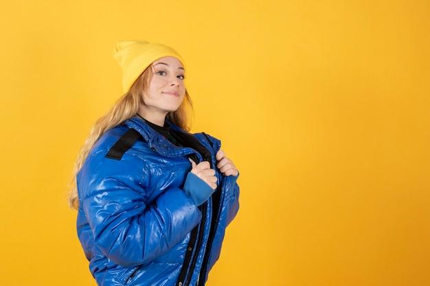 Kobieta w miejskich strojach, żółty kapelusz, żółte tło, nowoczesny