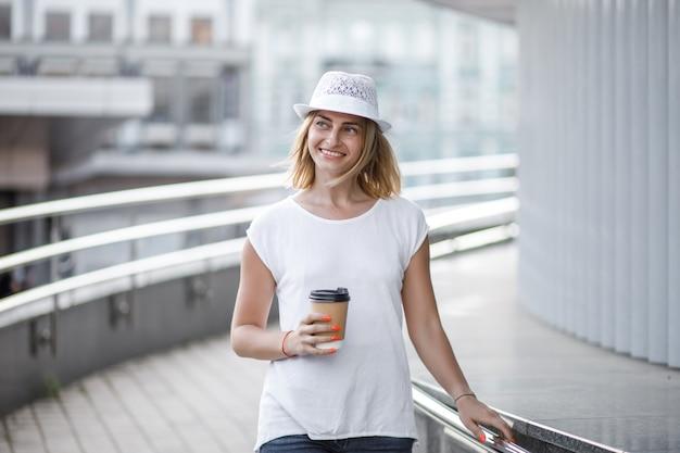 Kobieta w mieście z kawą, latem i słoneczną pogodą.