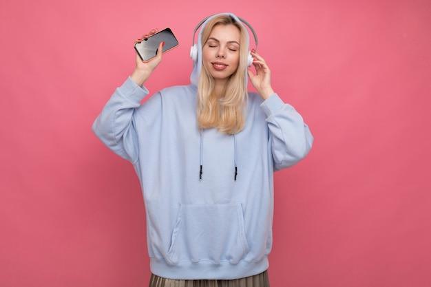Kobieta w modnej bluzie z kapturem słucha muzyki ze swojego telefonu