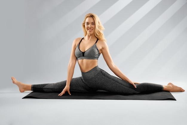 Kobieta w modnej szarej odzieży sportowej siedzi na sznurku