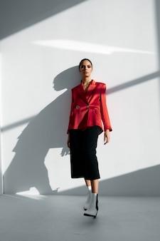 Kobieta w modnych jesiennych butach czerwona kurtka i czarne spodnie na jasnym tle
