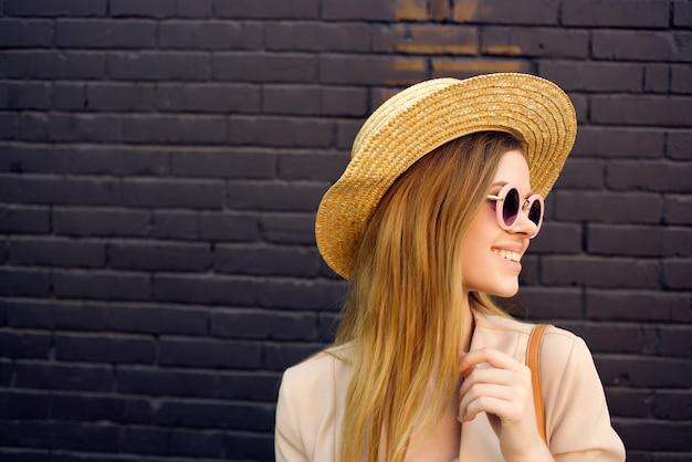 Kobieta w modnych ubraniach przy ścianie na zewnątrz spaceru w stylu ulicy