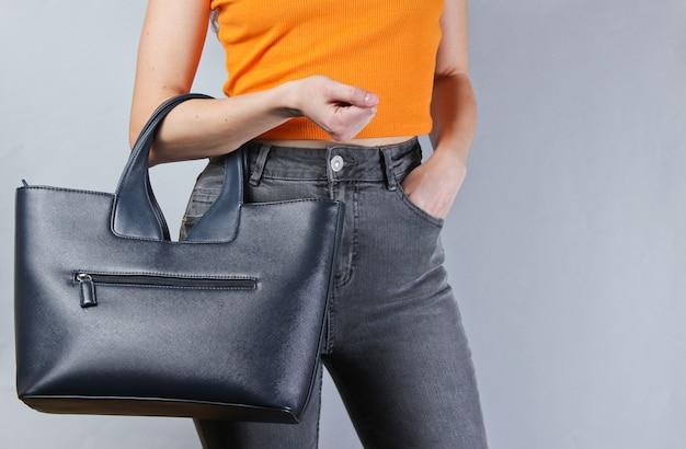 Kobieta w modnych ubraniach ze skórzaną torbą