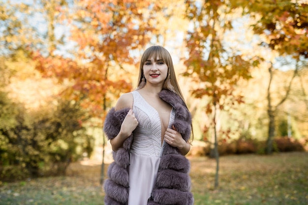 Kobieta w modzie beżowa sukienka i futro pozowanie w jesienny krajobraz. trendowe ubrania
