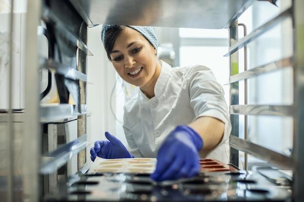 Kobieta w mundurze kuchennym wkłada wiele gumowych foremek do pieczenia cukierków w piekarniku lub na półkach