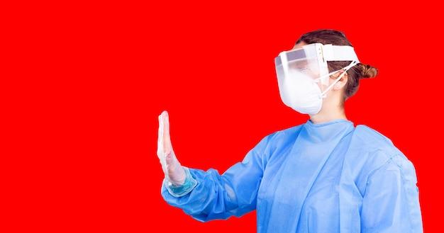 Kobieta w mundurze medycznym w rękawiczkach i plastikowej masce ochronnej pokazująca dłonią zatrzymanie korony...