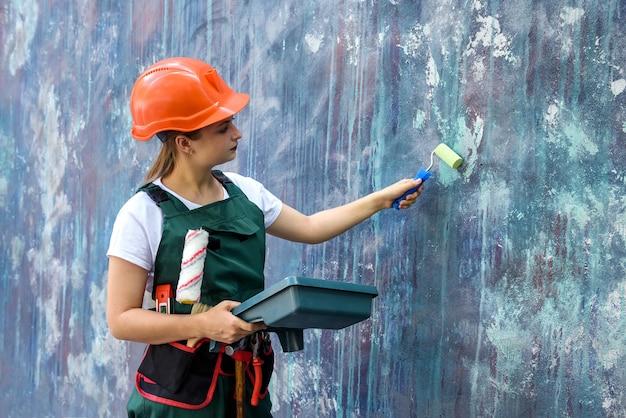 Kobieta w mundurze ochronnym, trzymając tacę i rolkę. ma hełm i pasek na narzędzia