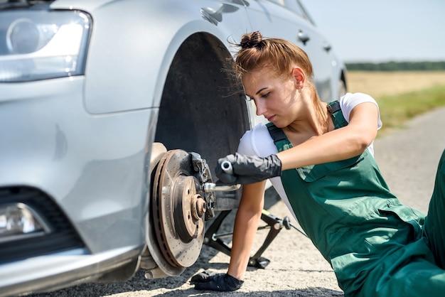 Kobieta w mundurze pracuje dla konserwacji hamulców samochodowych. naprawa samochodów. praca bhp