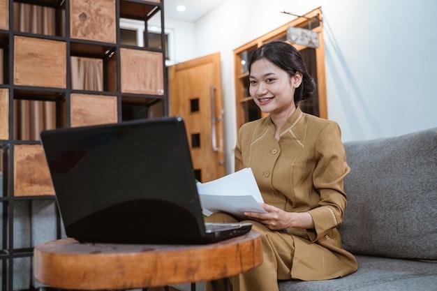 Kobieta w mundurze rządowym trzymająca dokumenty podczas pracy w domu online przy użyciu laptopa