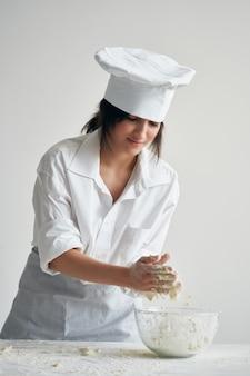 Kobieta w mundurze szefa kuchni pracuje z gotowaniem produktów z mąki ciasta