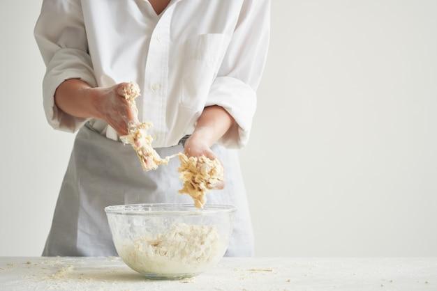 Kobieta w mundurze szefa kuchni ugniata ciasto na jasnym tle mąki stołu