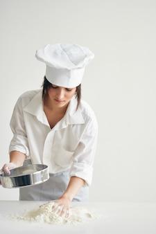 Kobieta w mundurze szefa kuchni wyrabia ciasto cebulowe kuchnia piekarnia gotowanie ciasta