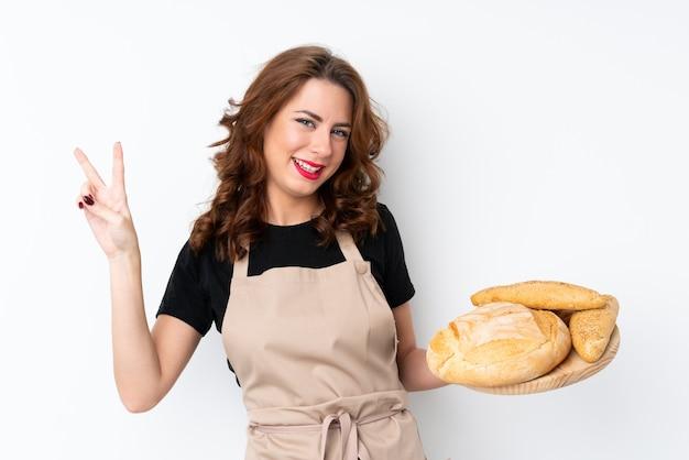 Kobieta w mundurze szefa kuchni. żeński piekarz trzyma stół z kilka chlebami uśmiecha się zwycięstwo znaka i pokazuje